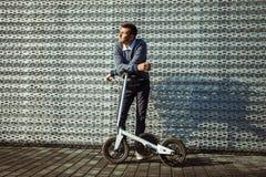 Man med sparkcykeln som rymmer en kopp kaffe mot bakgrunden av den moderna fasaden för stål arkivfoton