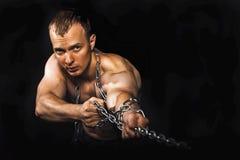 Man med starka muskulösa armar som drar kedjan Arkivbilder