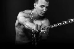 Man med starka muskulösa armar som drar kedjan Royaltyfria Foton