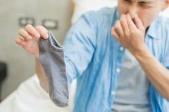 Man med stinkande sockor arkivfoto