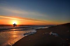 Man med surfingbrädan på den härliga soluppgångstranden Arkivbilder