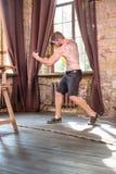 Man med tatoo på tillbaka boxning med dumbbels i händer Fotografering för Bildbyråer