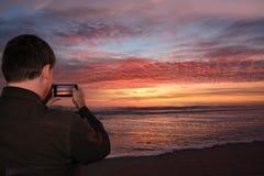 Man med telefonen på stranden på soluppgång royaltyfria bilder