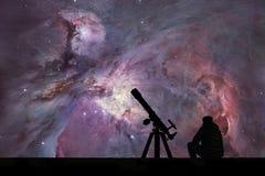 Man med teleskopet som ser stjärnorna Orion Nebula Arkivfoto