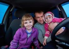 Man med två barn som sitter i bilen Arkivfoto