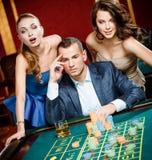 Man med två flickor som leker rouletten på kasinot arkivbild