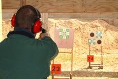 Man med vapnet för skytte för utfrågningskydd på pistolområde Royaltyfri Bild