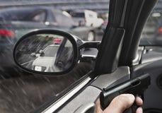 Man med vapnet i bil med polisbilen i sideviewspegel Royaltyfri Bild