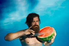Man med vattenmelon och kniven i pöl arkivfoto