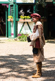 A man in mediaeval costume smokes sigar at Renaissance Festival. The Minnesota Renaissance Festival is a Renaissance fair, an interactive outdoor event which Royalty Free Stock Photo