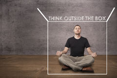 Man mediating and thinking outside of the box. Concept for thinking outside the box royalty free stock photo