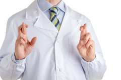 Man in medical coat crossing fingers royalty free stock photography