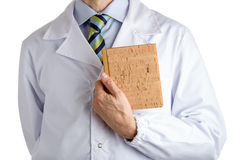 Man in medical coat holding blank cork book stock photo