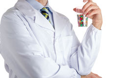 Man in medical coat holding plastic glass full of thumbtacks. Man dressed with medical white coat, light blue shirt and glossy regimental tie with dark blue stock images
