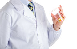 Man in medical coat holding plastic glass with pills. Man dressed with medical white coat, light blue shirt and glossy regimental tie with dark blue, light blue royalty free stock photography
