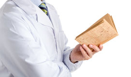 Man in medical coat reading blank cork book. Man dressed with medical white coat, light blue shirt and glossy regimental tie with dark blue, light blue and green Stock Photography