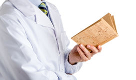 Man in medical coat reading blank cork book. Man dressed with medical white coat, light blue shirt and glossy regimental tie with dark blue, light blue and green Royalty Free Stock Photo