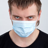 Man in medical mask. Portrait of pensive young man in medical mask royalty free stock photos