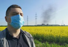 A man in a medical mask against the background of the plant. The concept of environmental pollution, ecology stock images