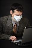 Man in medical mask diagnoses computer Royalty Free Stock Photo