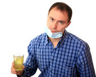 Man in a medical mask dissolves a pill Stock Image