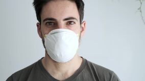 Man in a medical mask looks at the camera while at home isolation. Coronavirus pandemic, stay at home concept.