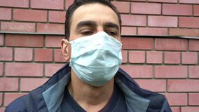 Man in medical mask out of breath, choking, suffocating, ill, heavy cough, breathless, suffer. Portrait