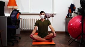 Man in a medical mask sits on the floor and meditates with a cat