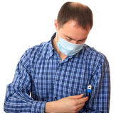 Man in a medical mask with a thermometer. Stock Images