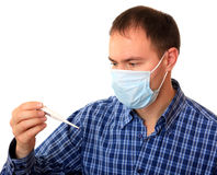 Man in medical mask with a thermometer. Stock Photos