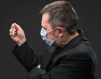 Man in medical mask with a thermometer Stock Photography
