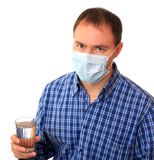 Man in a medical mask with water. Man in a non-permanent medical mask with glass of water Royalty Free Stock Photography