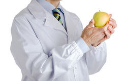 Man in medical white coat holding yellow apple Stock Images