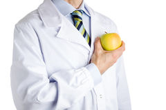 Man in medical white coat showing yellow apple Stock Image
