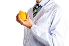 Man in medical white coat showing yellow lemon Stock Photography