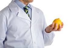 Man in medical white coat showing yellow lemon Stock Image