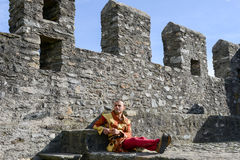 Man on medieval clothes sitting on the walls of Castelgrande. Bellinzona, Switzerland - 21 May 2017: man on medieval clothes sitting on the walls of Castelgrande Stock Photography