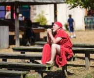 Man in Medieval Costume Renaissance Festival. Man in red medieval costume rests on wooden bench at Maryland Renaissance Festival Stock Images