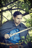 Man with medieval sword. Fantasy portrait of handsome dangerous man with medieval sword Stock Image