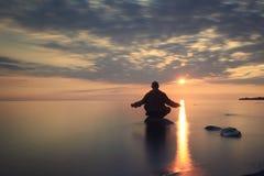 Man meditates on lake water Royalty Free Stock Photo