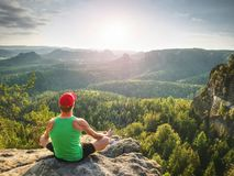Man meditates in yoga in mountains above wild nature at sunset. Concept of meditation, spirituality and soul balance. Man meditates in yoga position in mountains royalty free stock photo