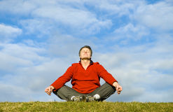 Man meditating. A forties man is sitting in a yoga position and meditating Stock Photography