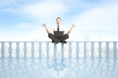 Man meditating on balcony pillars. Young businessman with laptop meditating on concrete balcony pillars. City and bright sky background. 3D Rendering Stock Photo