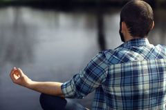 Man meditating on bank of  pond Royalty Free Stock Images