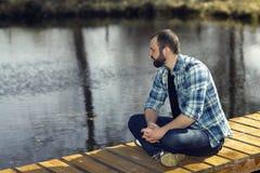 Man meditating on bank of  pond Stock Image