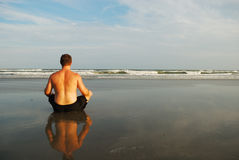 Man meditating on beach stock images
