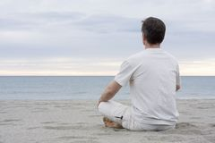 Man meditating on beach Stock Photos