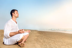 Man meditating on beach Stock Image