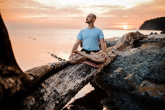 Man meditating on broken tree near sea sunset . Doing yoga outdoors royalty free stock image