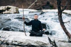 Man meditating with cliff on waterfall like sensei Stock Photos